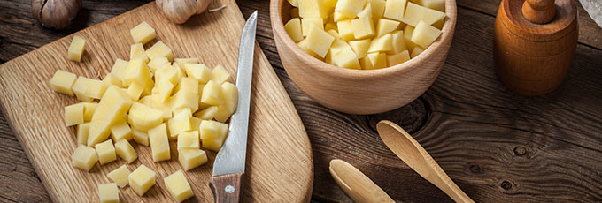 Diced potatoes on a wooden chopping board