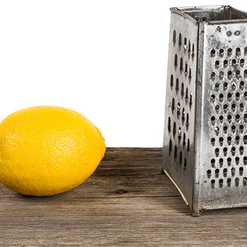 Cheese Grater And Lemon On Wooden Block