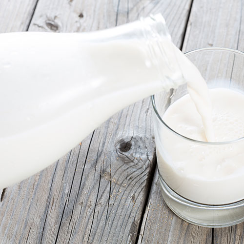 Pouring milk from a glass bottle